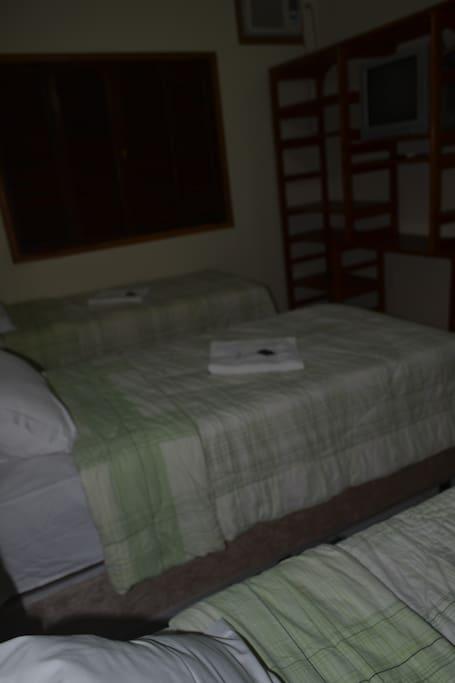 vista das camas de solteiro e prateleira para roupas