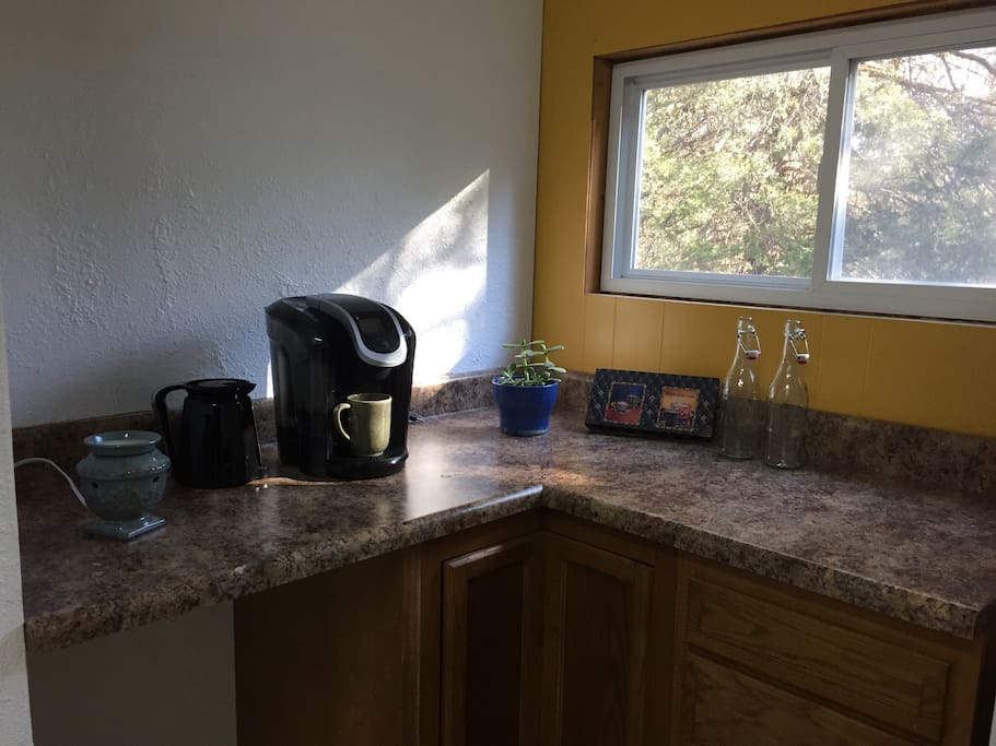 Keurig coffee brewer, and trees outside the kitchen window.