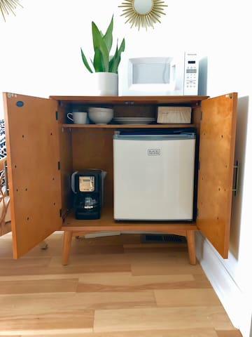 Kitchenette cabinet contains everything a traveler needs-- coffee maker, water kettle, mini fridge and dishes!