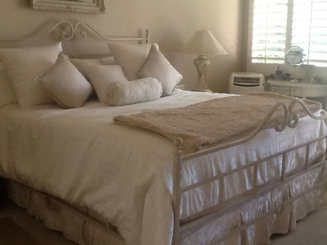 King Bed in Master Suite with vanity table and large TV