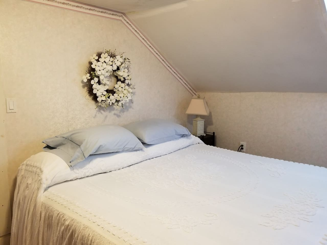 Cottage feel with a king size bed in original bedroom of home built in 1896.  Dresser and comfy chair too.  Quiet bedroom.