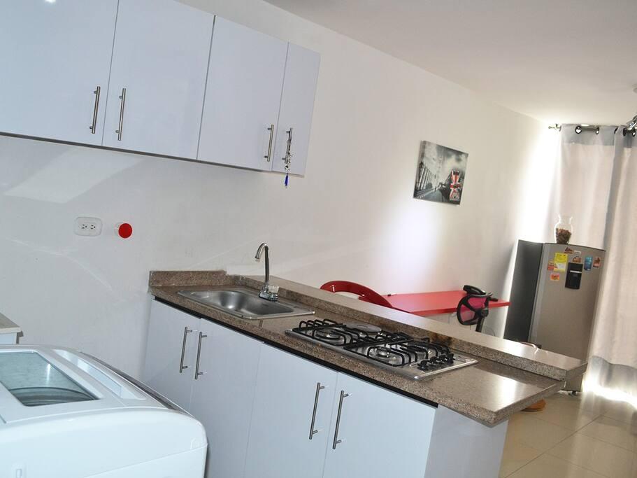 Cocina, sala, zona para trabajar con portátiles, lavadora.