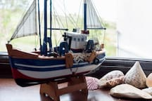 Boats and shells from the Atlantic and Pacific Oceans on the single room's windowsill.