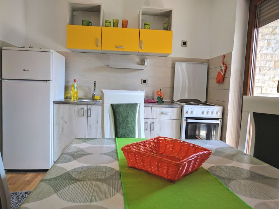Fully equipped kitchen with stove, dishes and fridge