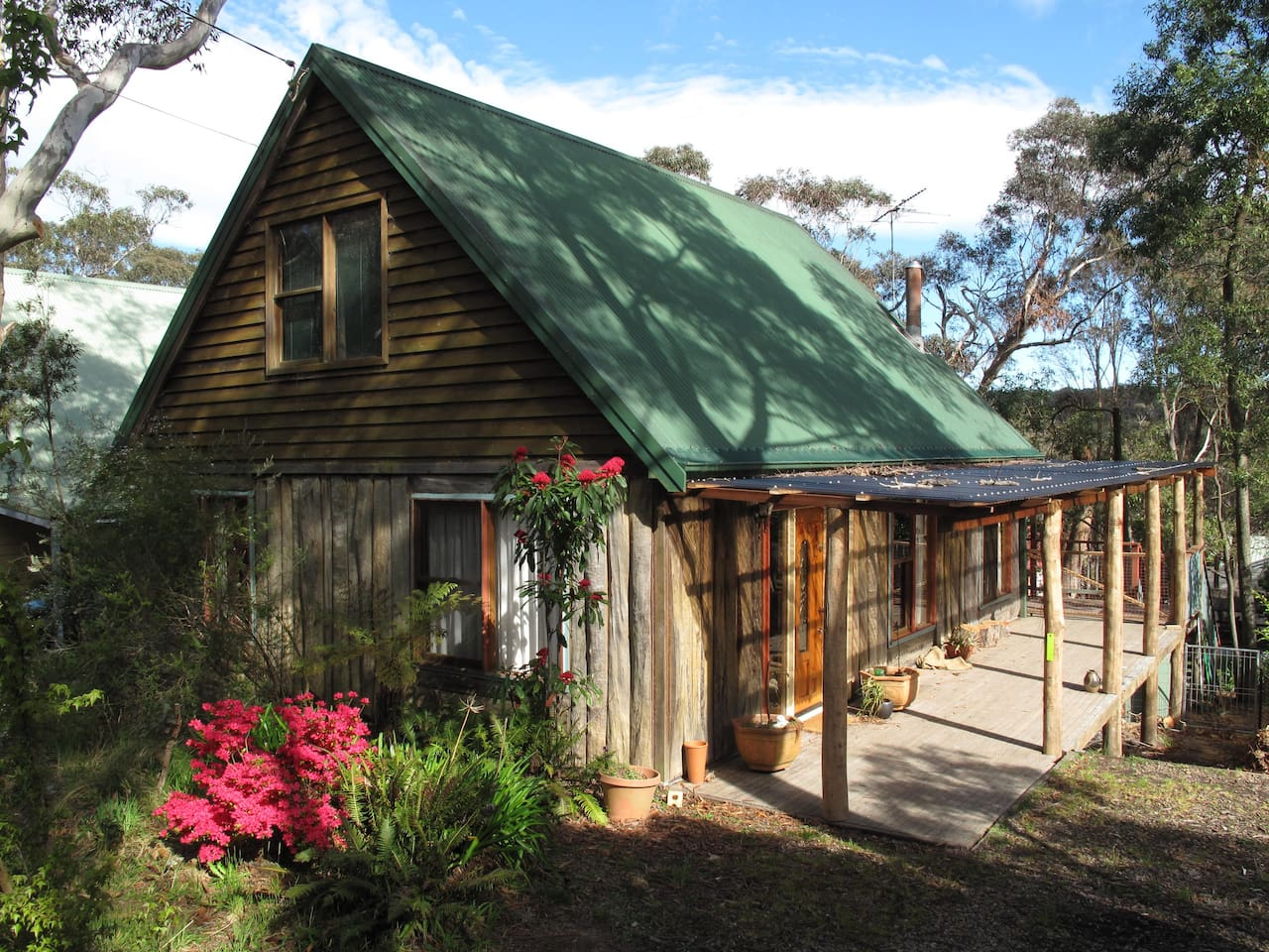 Our house as seen from the street. I built the verandah roof  from bush timbers to match the existing timber slab style construction.