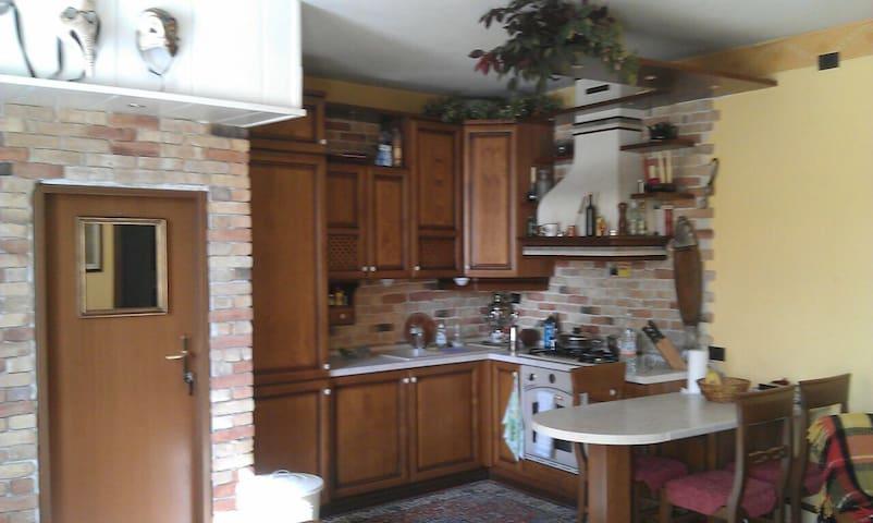 Angolo cucina con Frigorifero, Freezer, fuochi a gas. Porta di accesso al garage e zona lavatrice.