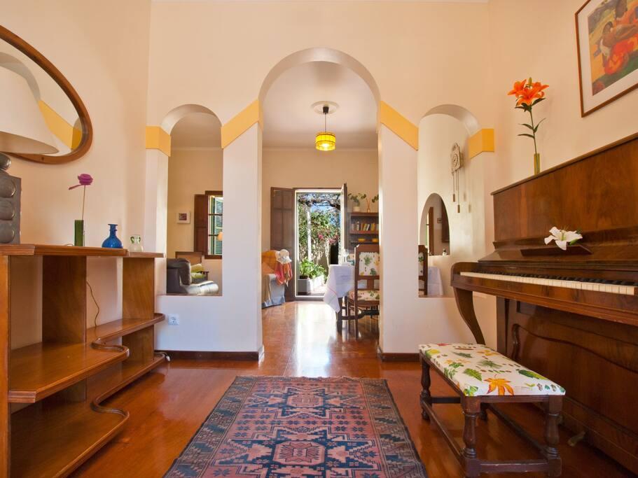 """Entrada en """"Casa Vivianne"""" con un piano y al fondo el patio"""