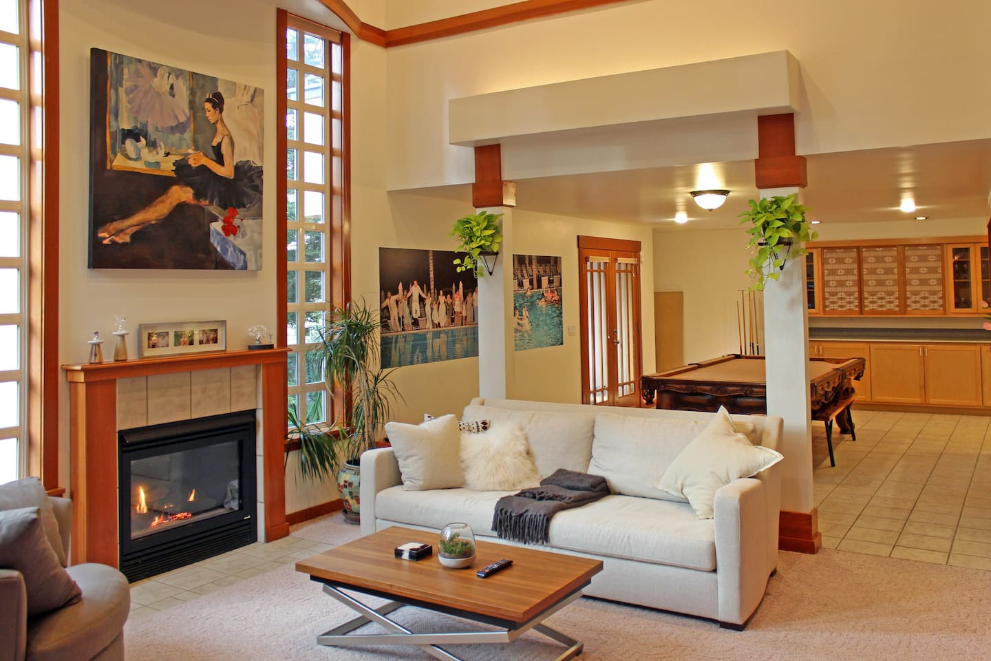 Spacious living room with vaulted ceilings, uplighting, fireplace, ultra-deep sofa and convertible dining table