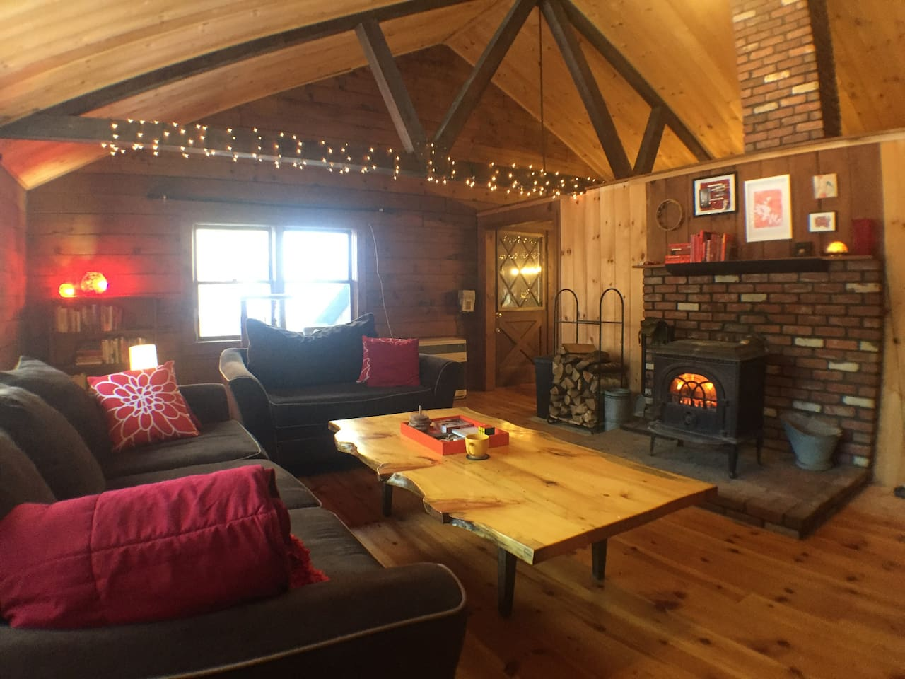 Spacious, open living room with cathedral ceilings and a cozy wood stove.