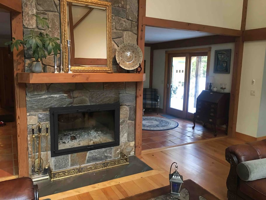Double-sided New England granite log fireplace graces the post-and-beam 'Great Room' with its 28-foot ceilings.