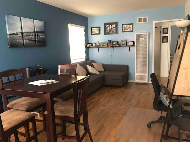 Dining area, living room, desk with printer, desk lighting and cords.