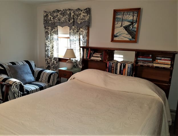 The queen bed and easy chair in Room 1.