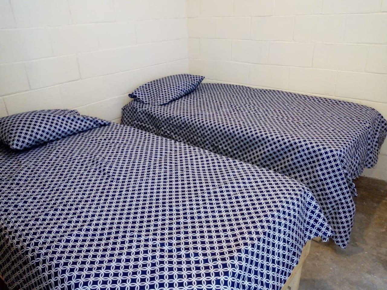 Una habitación con 2 camas individuales en primer piso, saliendo de la recamara esta ubicado el baño completo. Para entrar a la habitación condicionada se entra por la entrada principalmente de la casa.