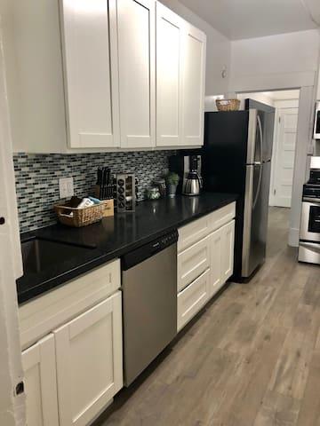 Kitchen with fridge, range, microwave, dishware and more!
