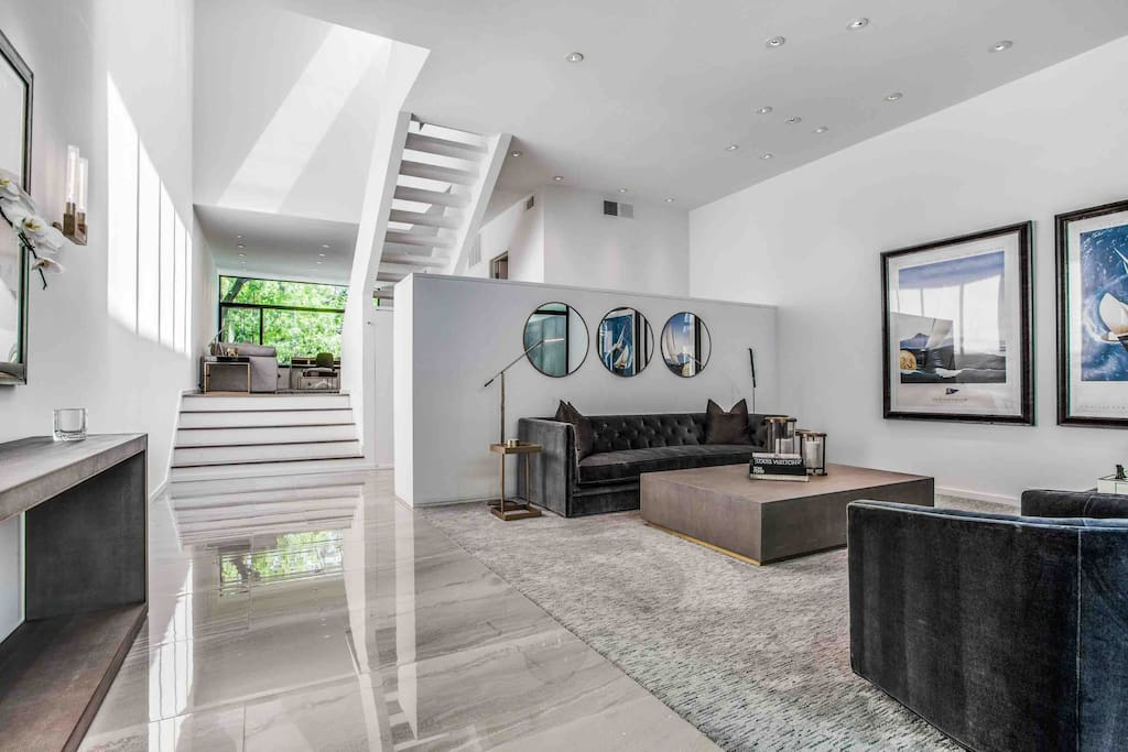 Main entry/Living room.  14 ft. High ceilings.  Gallery lighting.  Polished stone flooring.  Luxurious carpet, furniture and artwork!
