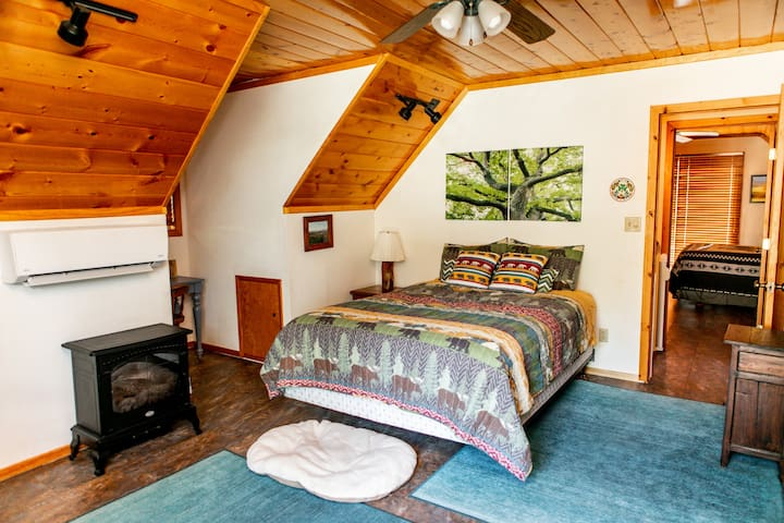 In the East bedroom, you literally sleep under an oak tree as you enjoy the warmth of the electric fireplace or the cool breeze from the air conditioner or just the open sliding glass door. Plus, you have your own private balcony to enjoy the treetop views.