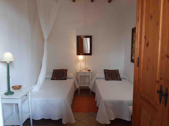 Dormitorio con dos camas individuales, armario y ventilador de techo. Bedroom with two single beds, cupboard and fan.