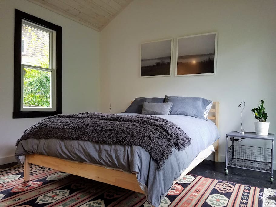 Cozy queen bed wrapped in a down comforter, with original art, live plant, on a gorgeous wool kilim.