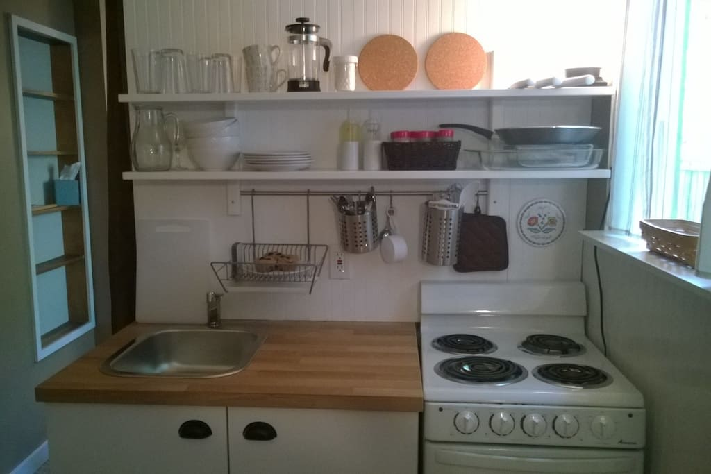 COVER #3 - Your kitchenette is stocked with basic dishes and cooking items. Spices, vinegar & oil, and coffee are on the shelves for your use.
