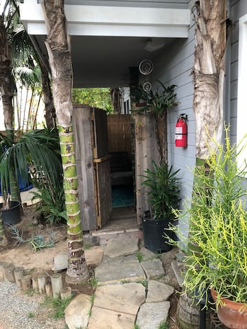 Private porch which has a that leads to tropical garden area! Gorgeous private and beach vibe. You can hear beach from your apartment and your porch!