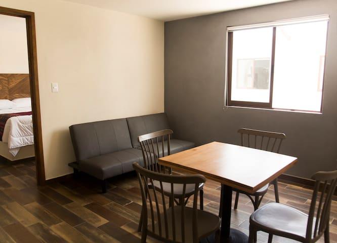 El Ciruelo. Acogedora habitación con cocina y sofá