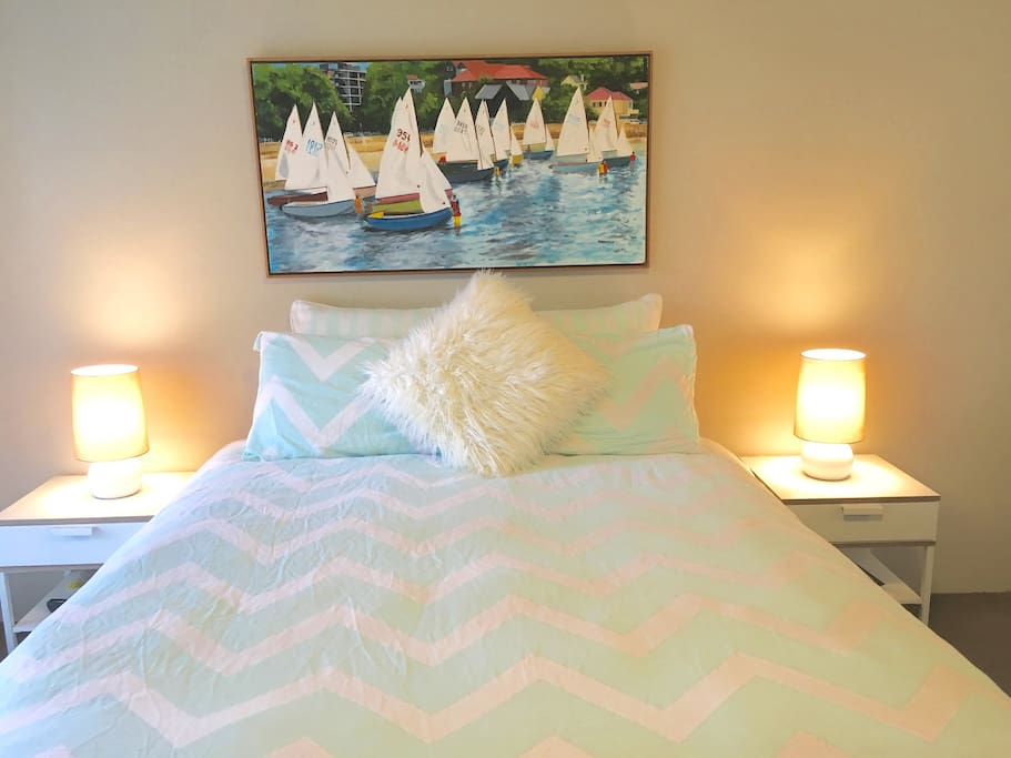 Queen bed in the main bedroom with painting of Double Bay harbour, only a 15 minute drive from the property.
