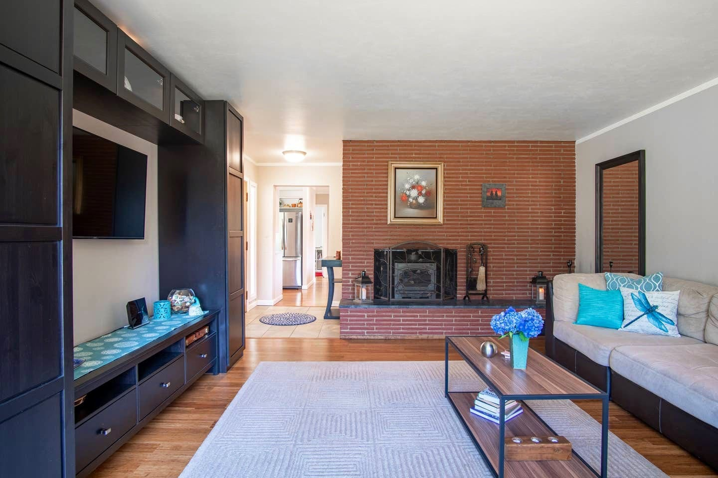 Living room area with relaxing indoor fireplace, full wall mirror, included WiFi, Smart TV, exercise equipment and fun games, cards and books included for entertainment.