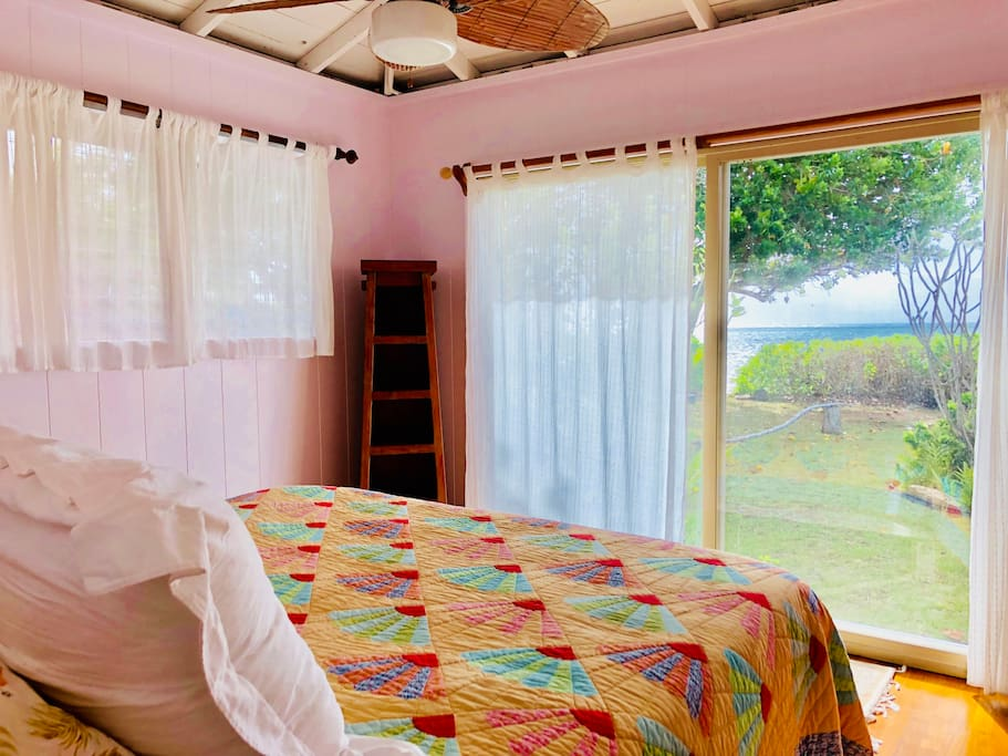 Oceanfront/master bedroom 1 with sheer curtains to provide privacy while allowing light. Large sliding glass door for easy access to outdoors and beach.