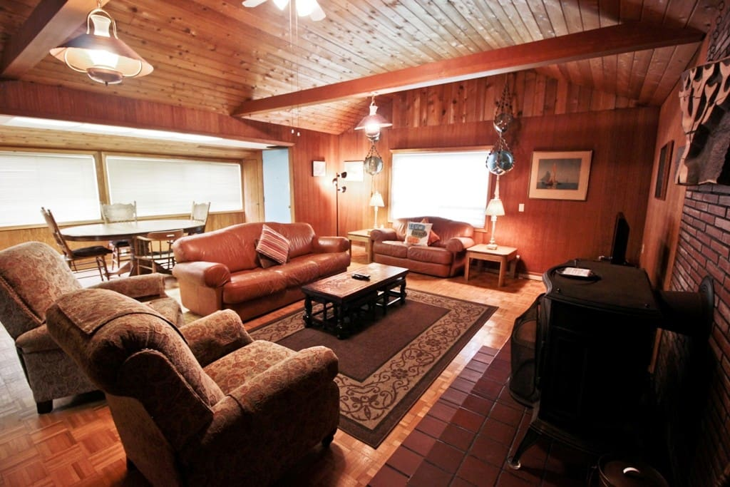 Living room with a flat screen cable TV/VCR/DVD player, wood stove, leather couch and love seat, two recliners, dining area for 5 and ocean views