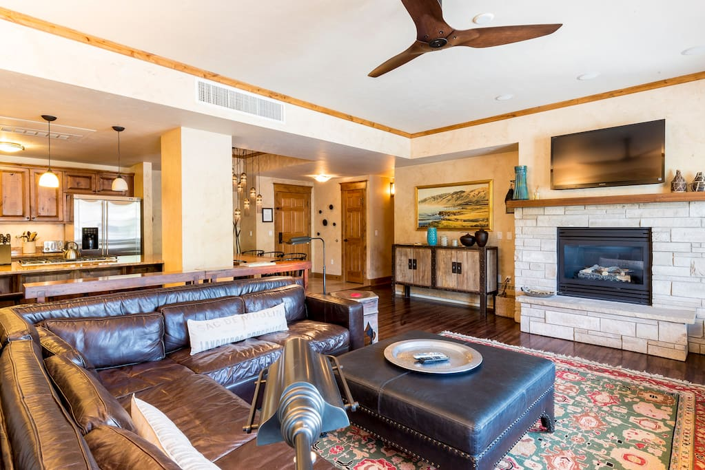 """A 47"""" flat screen TV mounted above a large stone fireplace in the main living room"""