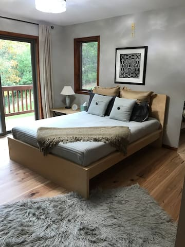 Queen platform bed with patio door axis to the deck.  8' closet with 6' louver doors!  The view is relaxing yet refreshing.  A room with a view!