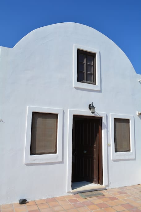 The villa with its traditional Cycladic architecture, showing the main entrance.