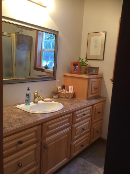 Beautiful bath with custom maple cabinetry, plush towels, plenty of toiletries.
