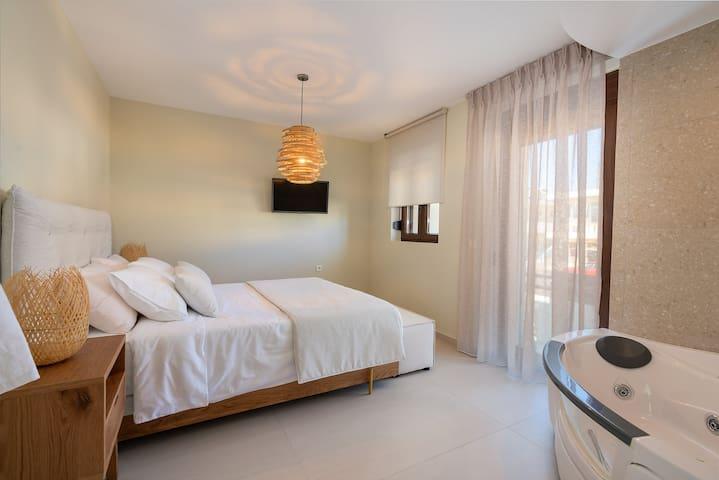 Bedroom with an en-suite jacuzzi bathtub.