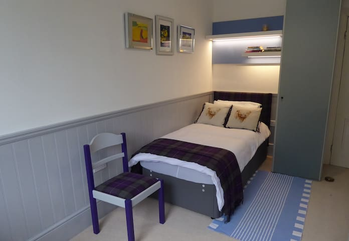 Comfortable bed, with wardrobe storage and modern lighting.