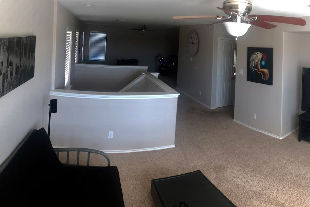 "Large common area featuring a 70"" smart tv with surround sound, full size futon and an Apple TV"