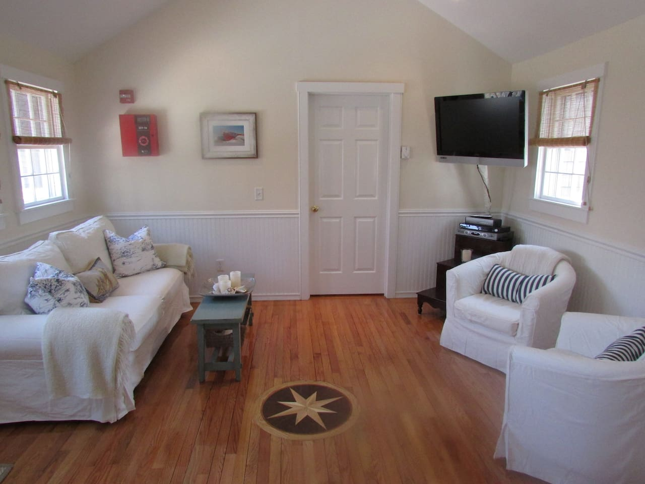 Front living room area with hardwood floors (and wooden compass inlay), flat screen tv, couch