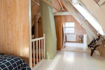 The whole attic room is open plan, the bed, sitting area and bathroom are all in one area.