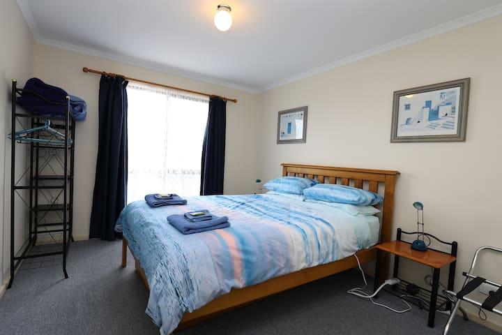 Bedroom #1 with queen bed, dual electric blanket, suitcase rack & garment rack