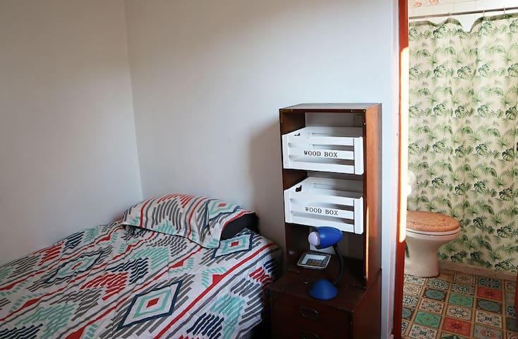 Se ve la cama (de plaza y media), el velador, y el baño privado. Además, la habitación tiene un closet y perchero (que no se ve en la foto).