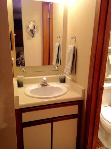 Room vanity and sink. Extra towels and first aid kit in cupboards below.