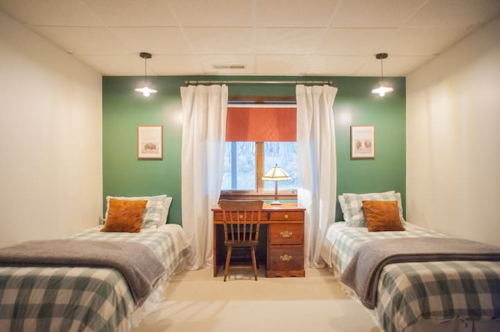 Bison room featuring twin beds and desk.