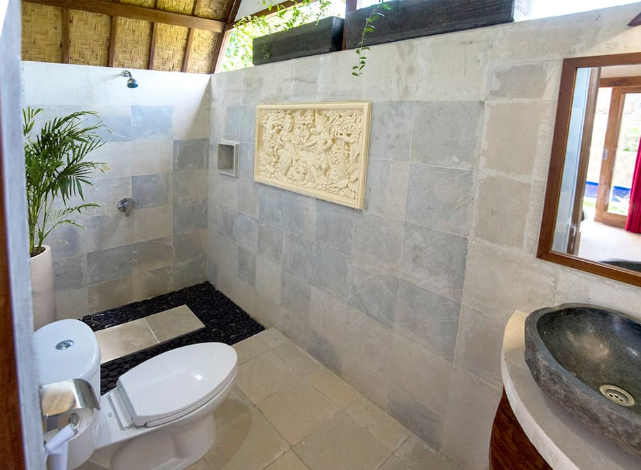 Cool open style stone finish bathroom with shower and hot & cold water