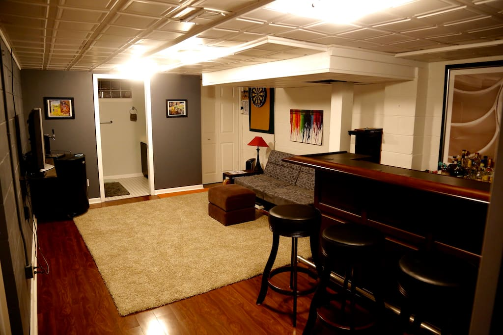 Living area with flatscreen tv, Apple TV, DirecTV, and a DVD player, and a dart board.