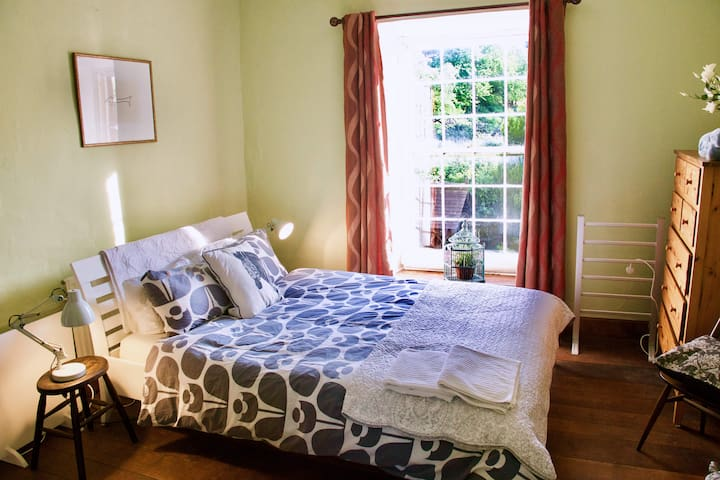 Your comfy en-suite bedroom awaits, complete with a view of green fields