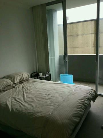 Bedroom with built in wardrobe and private balcony with TV.