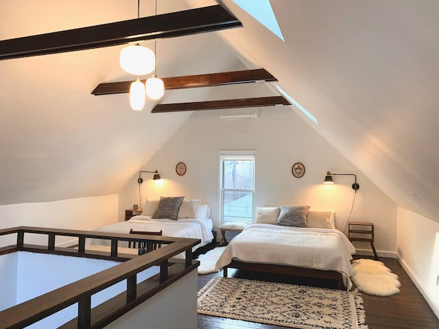 The upstairs sleeping area is one light-filled large room with cathedral ceilings. There are two queen beds in the space and plenty of room for additional sleepers on an inflatable mattress. We also have an infant bed we can set up for little ones.