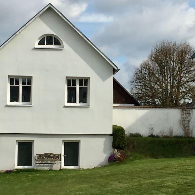 Sitzplatz in der Sonne, darüber Wohnzimmerfenster und Dachluke