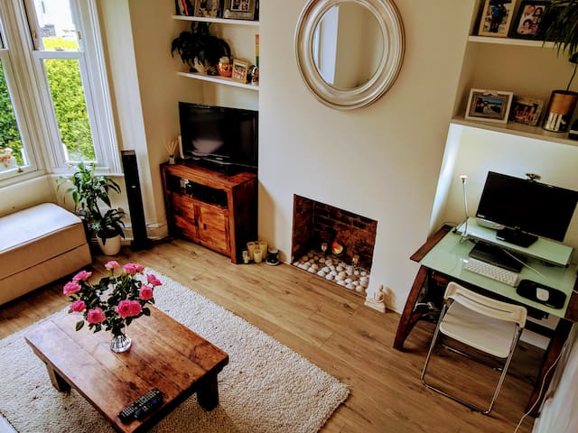 Living room - TV includes all UK Freeview channels, Netflix and YouTube with surround sound system. Additional desk space in corner.