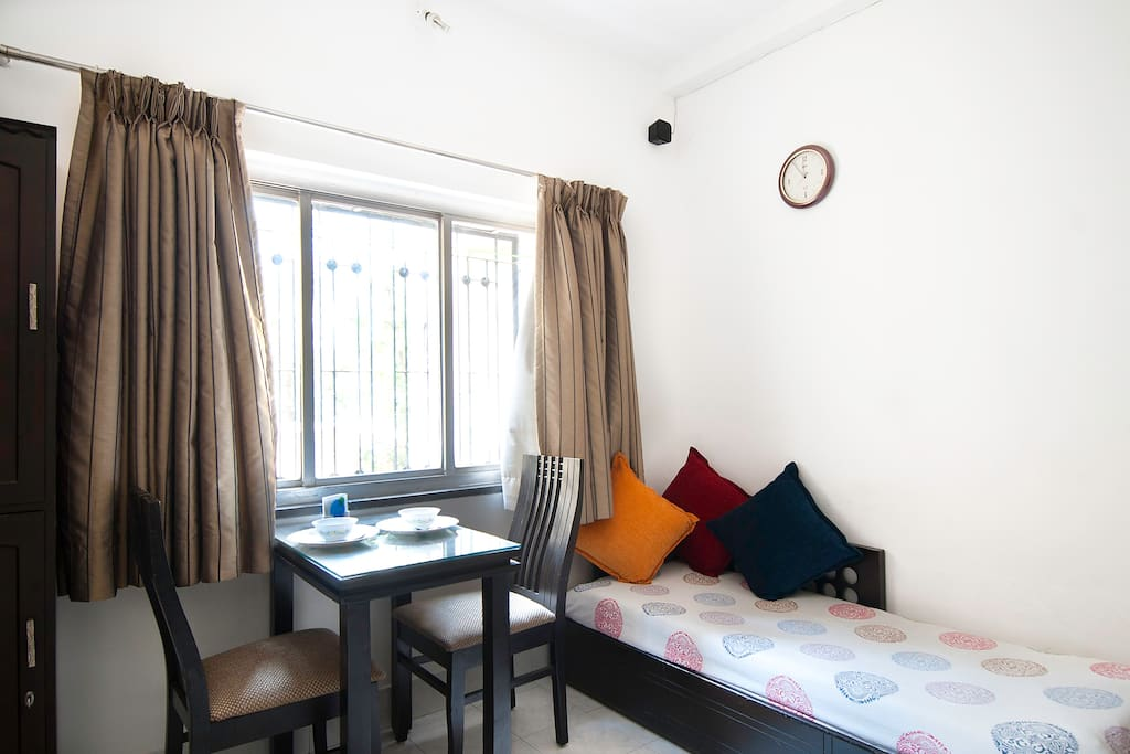 Abundant sunlight in the room with a dining table for two. The cot can be opened up in a double bed that accomodates two